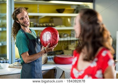 Salesman holding gouda cheese and interacting with costumer in grocery shop