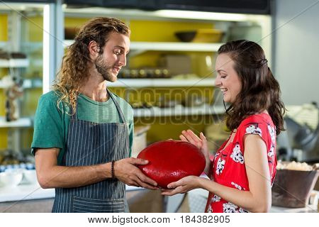 Salesman assisting costumer in buying gouda cheese at counter in grocery shop