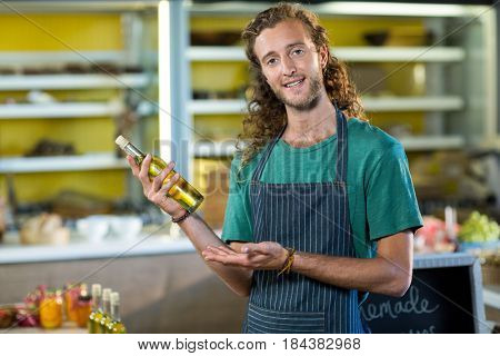 Shop assistant showing a bottle of olive oil at grocery shop