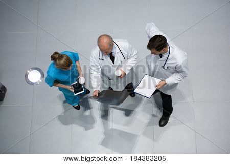 Doctors and surgeon discussing x-ray while having coffee in hospital