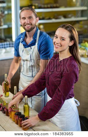 Portrait of shop assistants arranging jam and pickle jars at grocery shop