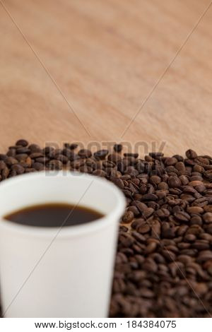 Coffee beans and black coffee in disposable cup on wooden background