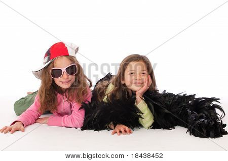 Two Friend/sisters in fancy dress lying on floor Smiling