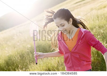 Hispanic girl running in field with net