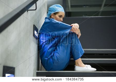 Thoughtful female surgeon sitting on staircase in hospital
