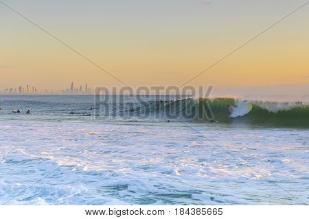 Surfers riding big waves at sunrise on the Gold Coast. Surfers Paradise in the horizon
