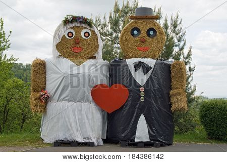 Two figures made out of straw bales, dressed like bride and groom