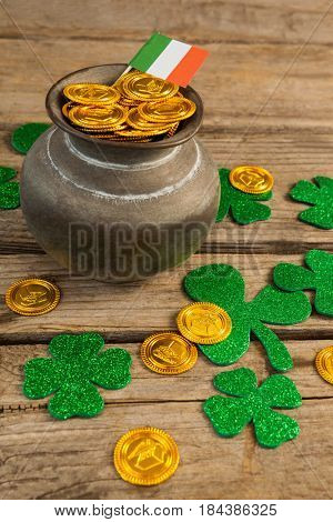 St. Patricks Day pot of chocolate gold coins with irish flag and shamrocks on wooden table
