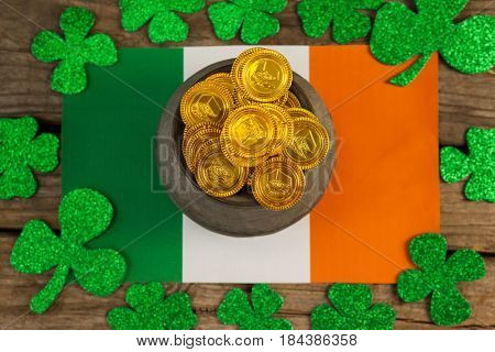 St. Patricks Day pot of chocolate gold coins and irish flag surrounded by shamrock on wooden table