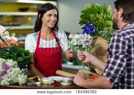 Florist receiving payment from customer at florist shop