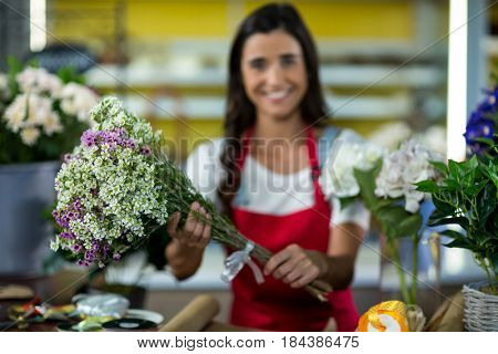 Florist offering flowers at the counter in the florist shop