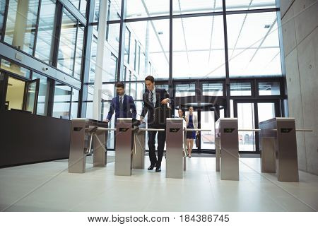 Businesspeople scanning their cards at turnstile gate in office