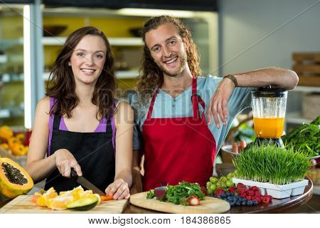Portrait of two shop assistant chopping fruits at the counter in health grocery shop