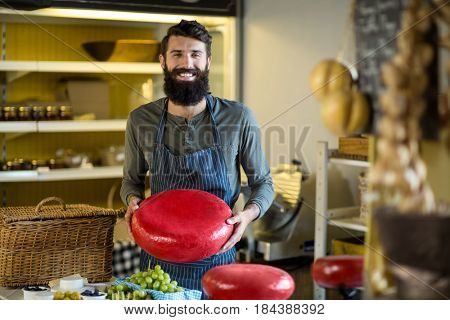 Smiling salesman holding a gouda cheese at grocery shop