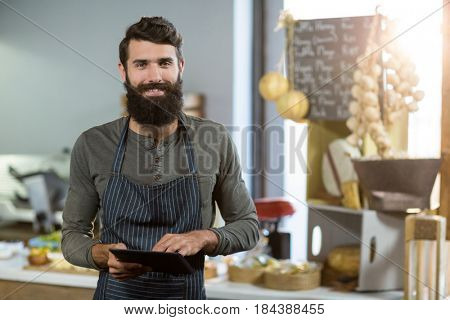 Portrait of salesman using digital tablet at counter in grocery shop