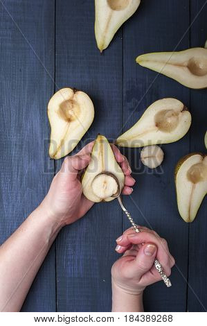 The pear halves with spoon on dark blue wooden table. Woman hands with half pear and spoon.