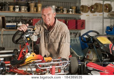 Hispanic mechanic working on go-cart