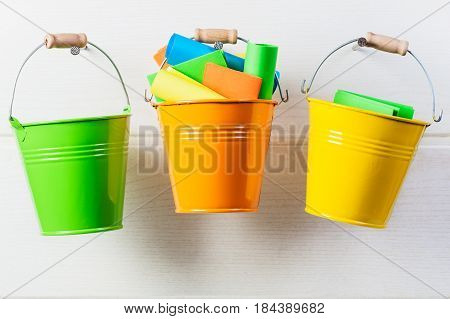 Bucket list concept. Buckets with colorful paper notes hanging on white wooden wall