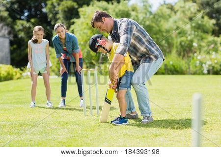 Happy family playing cricket together in backyard