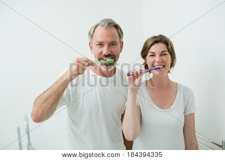 Portrait of couple brushing their teeth with toothbrush at home