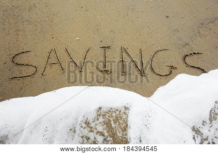 Savings text written in the sand being washed away by a wave -- Financial insecurity concept