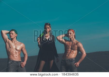 cool hot fashionable criminal woman bandit has dreadlocks with baseball bat near muscular men with sexy body and wet torso in jeans on natural background