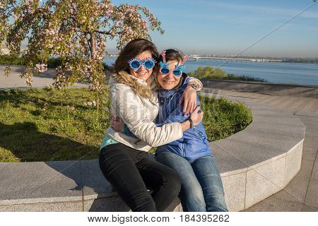 Happy Mother And Adult Daughter In A Funny Sunglasses Are Hugging And Having Fun