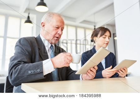 Senior citizen reading internet online message on tablet computer