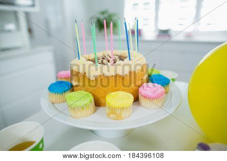 Close up of birthday cake on stand with cup cake and candles in kitchen