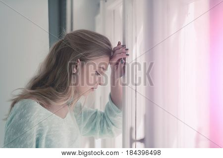 Praying or meditating. Pretty girl or young woman with closed eyes on cute face and blond long hair standing at window on sunny day.