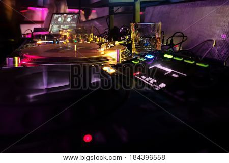 Professional dj equipment record turntables and mixer with vinyl disc in night or dance club. Colorful neon lights on dark background. Nightlife music entertainment