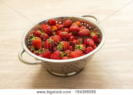 Fresh strawberries in a colander on a light background. Healthy helpful food.