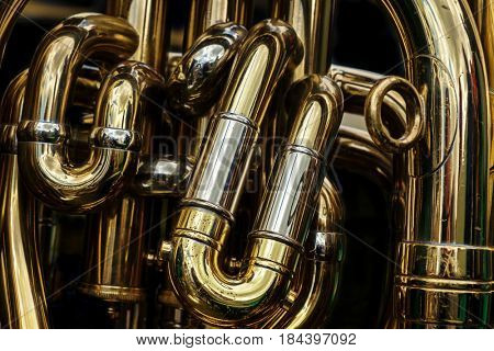 Detail of the brass pipes of a tuba. Abstract background showing the curves and joints of this polished brass band musical instrument.