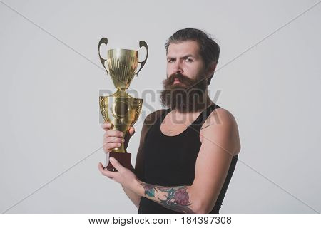 Bearded Serious Man Holds Gold Champion Cup On Grey Background
