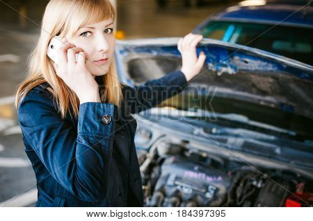 Portrait Of Blonde Woman In Black Cloak Calling Phone In Car Service For Help, Lifting Hood Of Car A