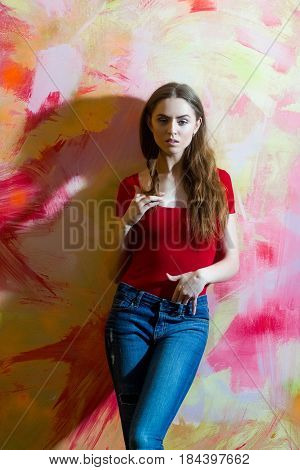 Pretty girl or beautiful woman twirling long blond hair wearing red tshirt and blue jeans on pink and yellow abstract wall