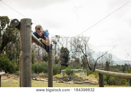 Woman jumping over the hurdles during obstacle course in boot camp