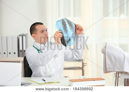 Handsome young orthopedist working in office