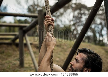 Determined man climbing a rope during obstacle course in boot camp