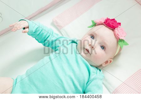Infant lies on her back in a baby crib. Baby is dressed in a suit for babies.