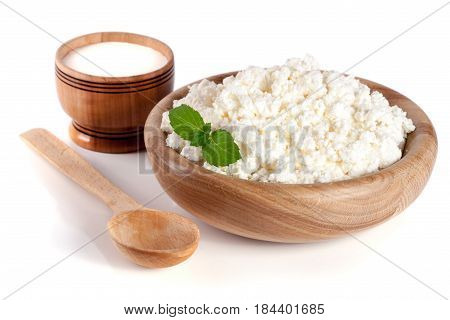 Cottage cheese in a wooden bowl isolated on a white background.