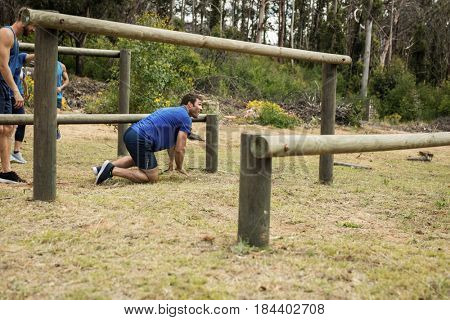 Man passing through hurdles during obstacle course in boot camp