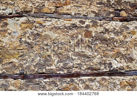 Wall of old stone with wooden inserts