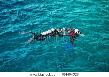 underwater snorkeling divers in wetsuits equipped with snorkels scuba aqualung diving masks swim fins swimming in sea or ocean water on sunny day on blue background. Idyllic summer vacation