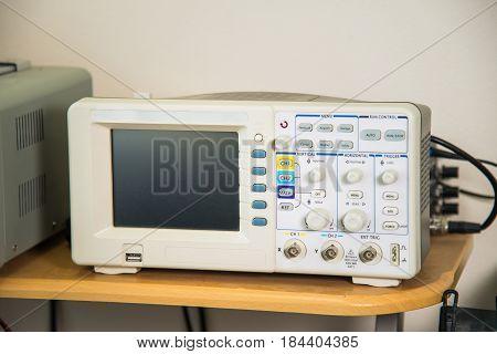 Modern oscilloscope in repair service, technical equipment, blank screen, no graph.