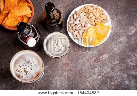 Beer in bottles and glasses on the concrete table. Beer and snacks are pistachio nuts chips and nachos top view. Copy space. Drink and snack for the football match or party