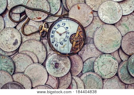 A bunch of old silver coins with a broken pocket watch on top