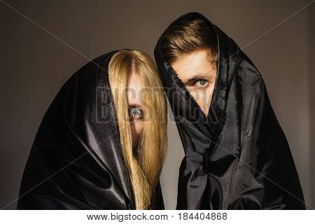 The anonymous girl with long blonde hair and a man in black cloth on faces. Conceptual anonymous photography. Piercing look. Anonymity. Portrait anonymous photography.