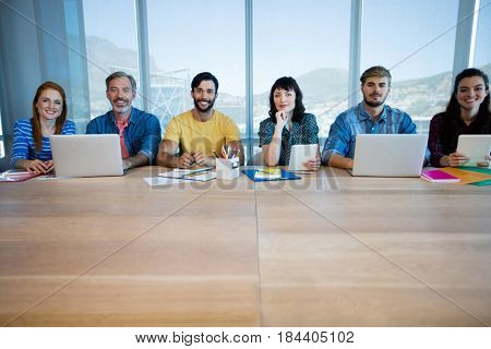 Portrait of creative business team sitting in a row and working together in office