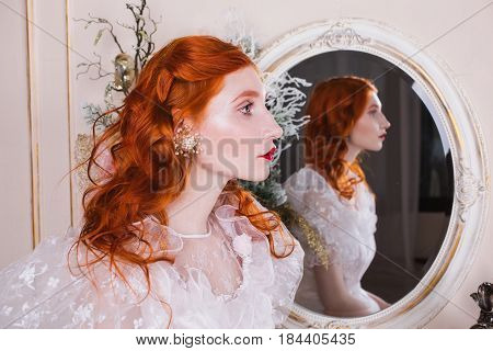 Portrait of perfect woman with long red curly perfect hair in a white perfect vintage wedding dress with white pearl earrings on her ears. Red-haired perfect girl with a pale skin, blue eyes, a bright unusual appearance in bedroom. Perfect model